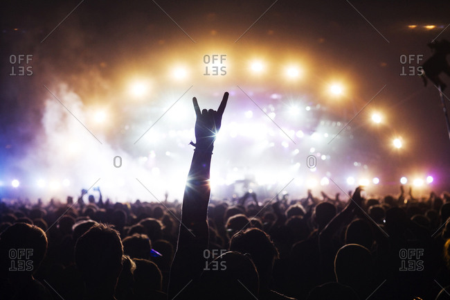 Amused festival goers and music fans attend another live concert at a music festival. A find is showing the sign of the horns with his hand.