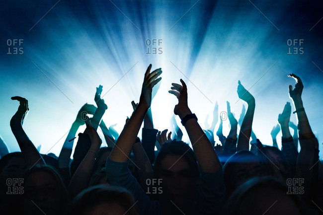 A concert crowd is putting the hands in the air during a live concert at a music venue.