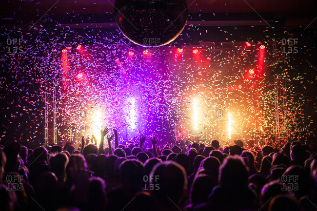 Festival crowd are enjoying good time at a live concert with the air full of confetti.