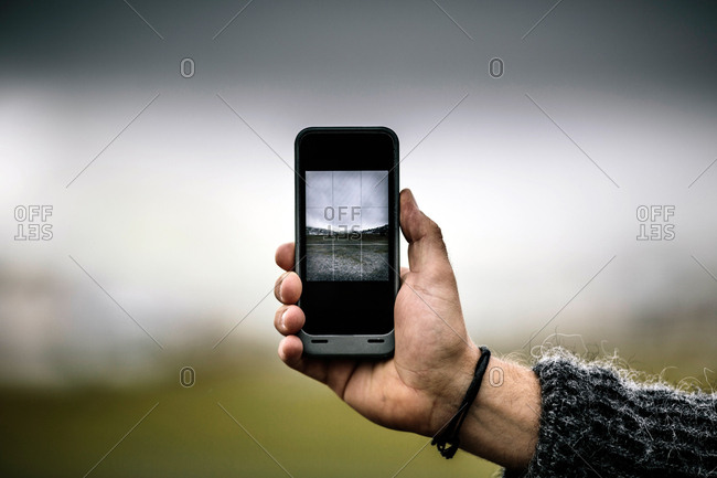 A person is taking a picture of the landscape in the Faroe Islands with a smart phone.