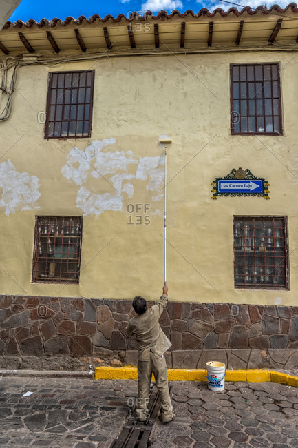 June 6, 2016 - Cusco, Peru: Man painting exterior of house