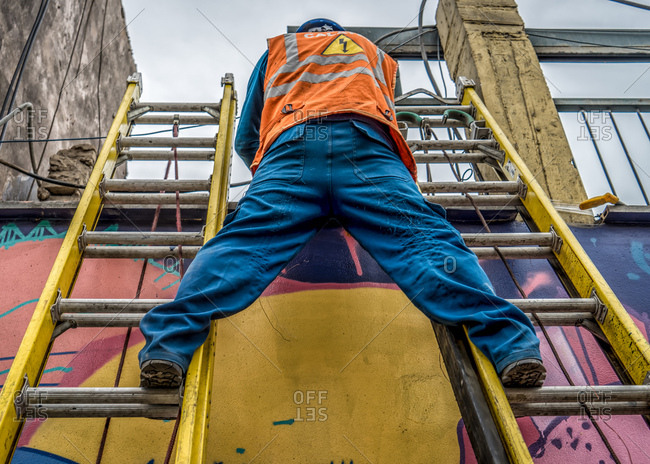 Worker straddling two ladders against wall with mural