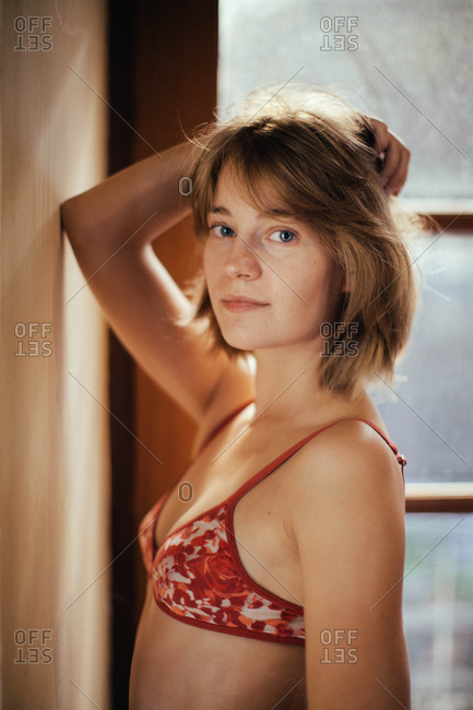 Portrait of a young woman inside in her bra in front of a sunny window