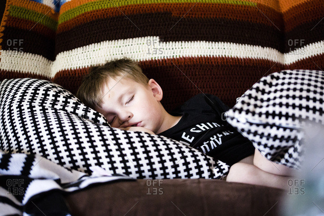 Boy napping among couch pillows