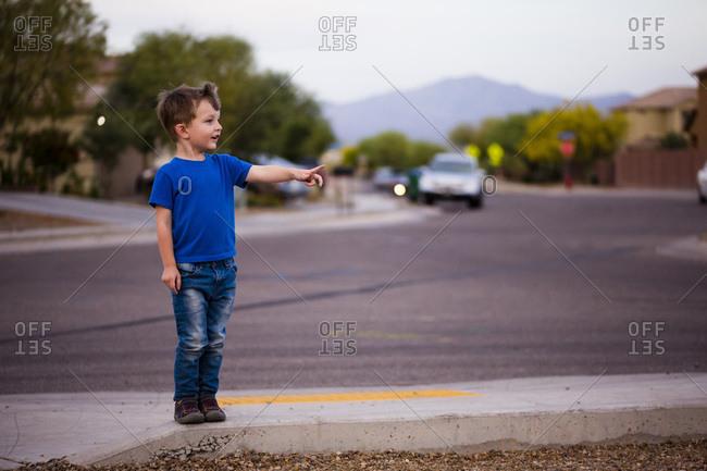 Boy pointing on sidewalk by street