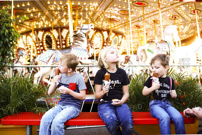 Kids eating corn dogs by carousel