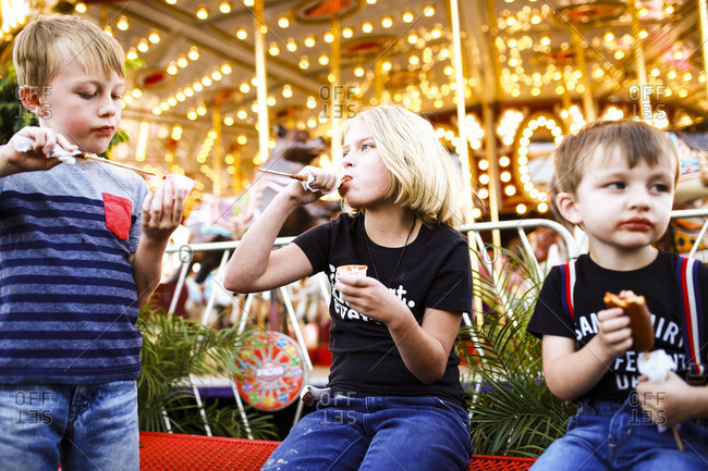 Kids eating corn dogs by a carousel