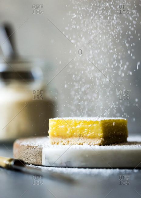 Sprinkling sugar on a lemon tart cake