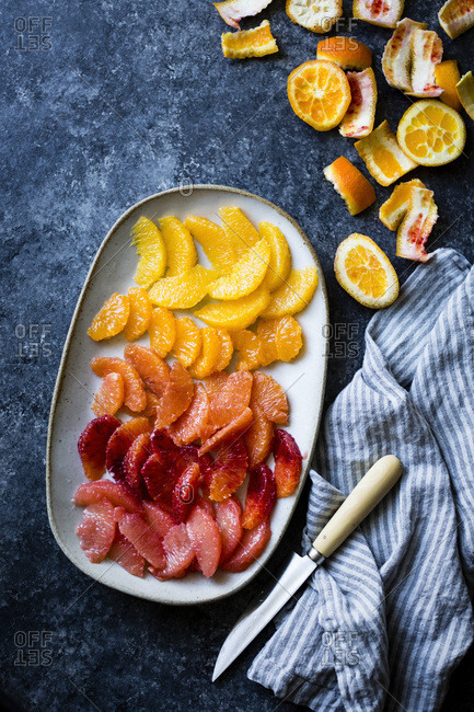 Various citrus fruits on a plate, all sliced and in segments