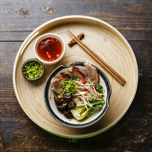 Rice noodles with boiled pork, wheat germ and shiitake mushrooms on wooden background