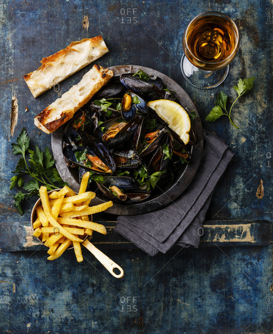 Mussels on metal plate, baguette toasts, French fries and wine on blue background