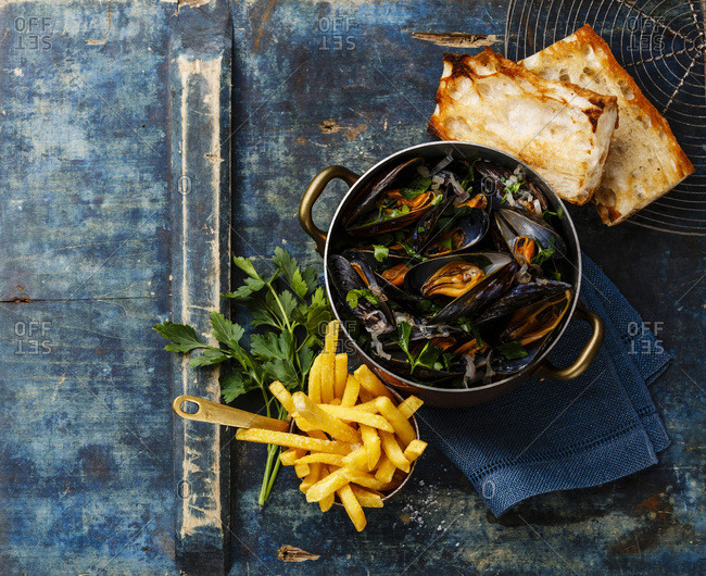 Mussels in copper cooking pan, baguette toasts and French fries on blue background