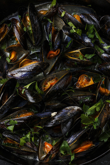 Mussels in black cooking pan with parsley close-up