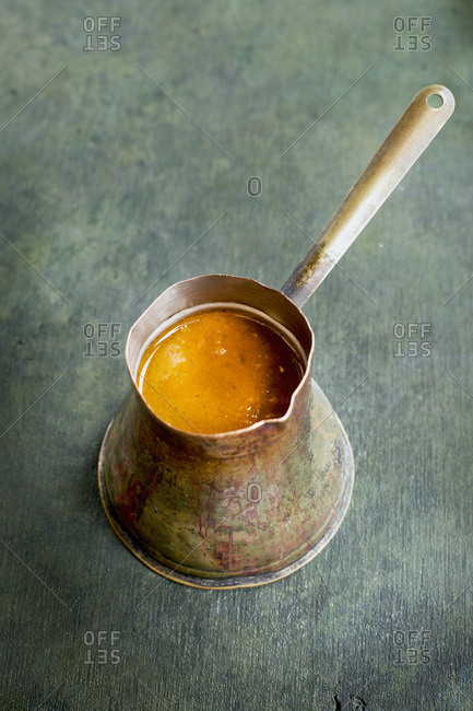 Ranchero Sauce in a vintage copper ladle.  Photographed on a green background.