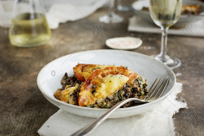 Wild Rice Kale Tomato Casserole with a Cheddar Cheese Sause served with white wine. Photographed on a rustick brown/black background.