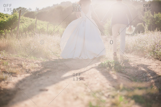 Bridal couple in sunlight in field