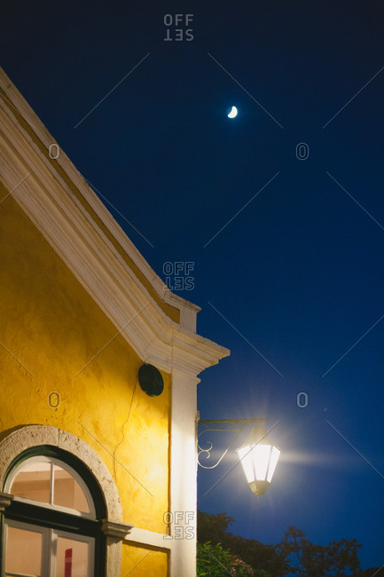 Streetlight on house beneath moon