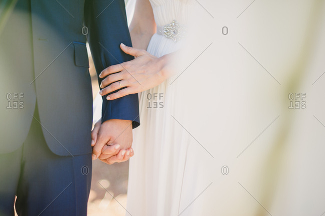 Bride and groom lovingly hand in hand