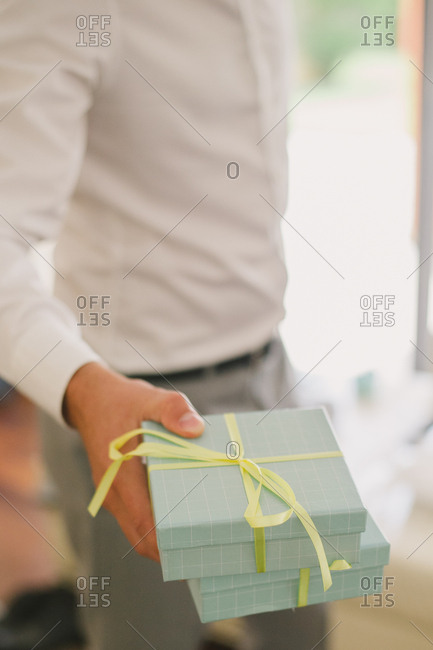 A groom holding gift boxes