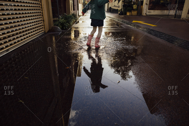 Young girl jumping in puddle