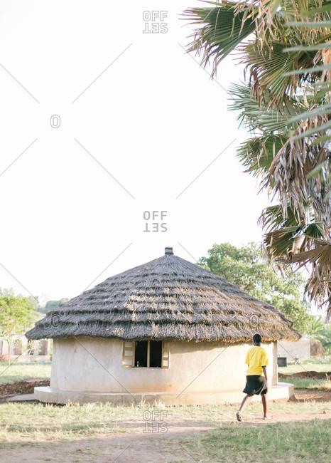 Woman walking past hut in Africa