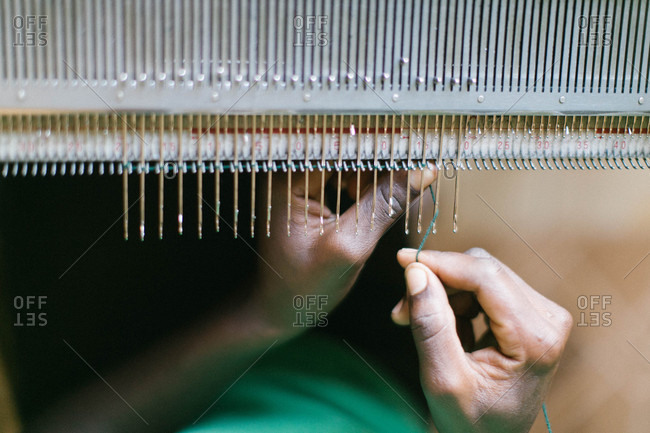 African person threading string onto hooks