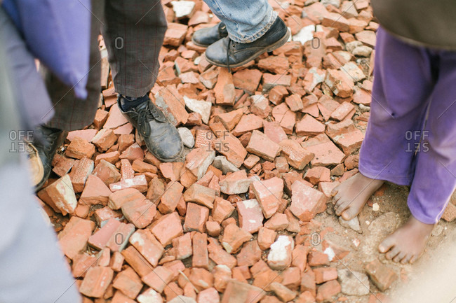 People standing on pile of broken red bricks