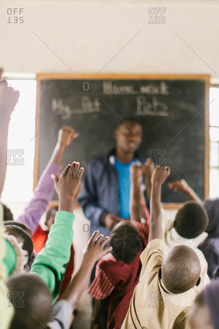 Children raising hands in a classroom in Africa