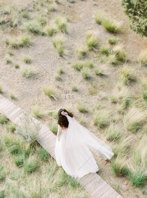 Bride walking on a crooked wooden boardwalk
