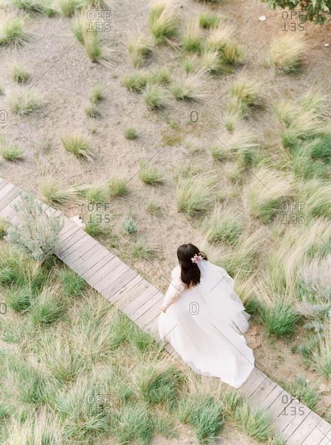 Overhead view of bride walking on a crooked wooden boardwalk