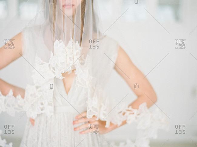Bride wearing sheer veil with her hands on her hips