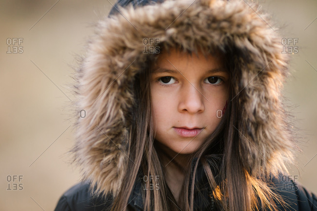 Portrait of young girl wearing winter jacket with furry hood