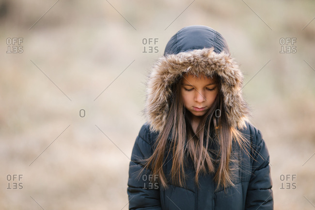 Young girl wearing winter jacket with furry hood looking down