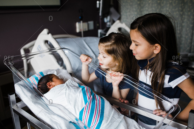 Sisters looking into hospital bassinet at baby sister