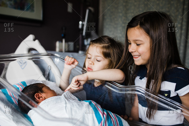 Two sisters looking into hospital bassinet at baby sister