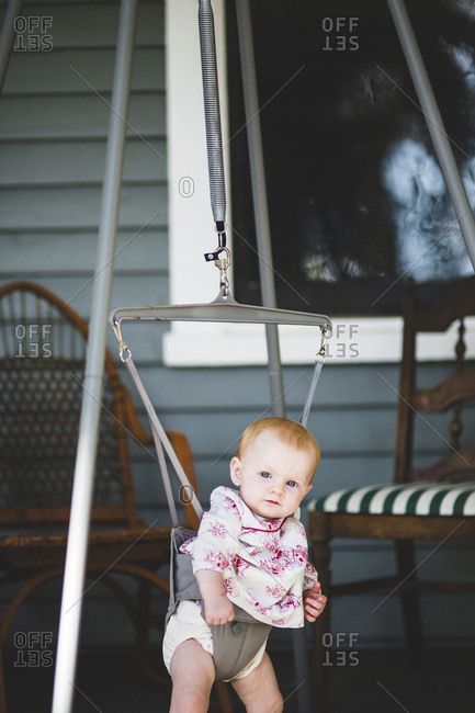 Baby girl in a jumper on porch