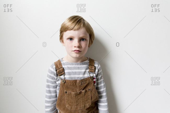 Portrait of a boy with strawberry blonde hair and freckles wearing overalls