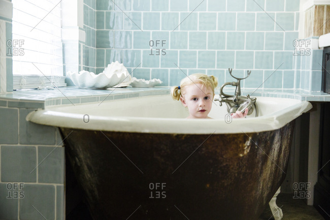 Little girl taking a bath in vintage tub