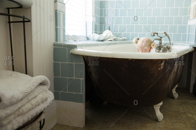 Little girl taking a bath in vintage claw foot tub