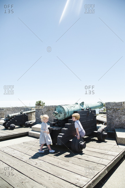Brother and sister standing next to cannon at historic fort in Saint Augustine, Florida