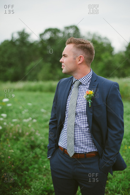 Groom in suit standing in field