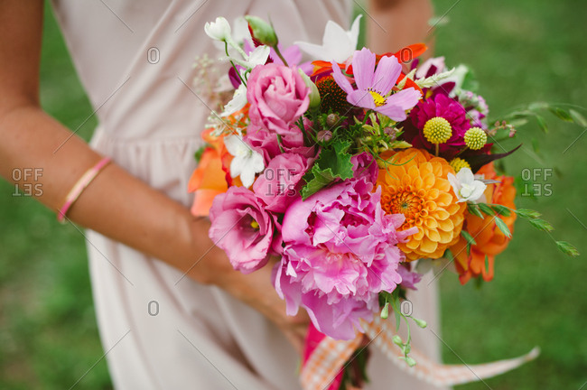 Colorful bouquet of flowers in hands of bridesmaid