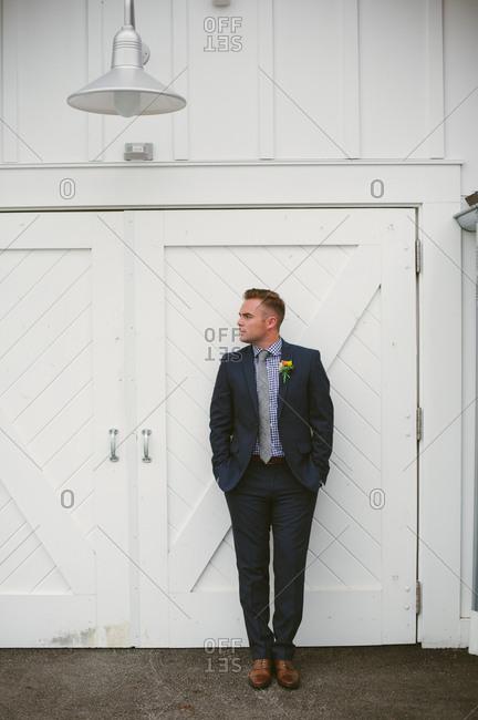 Groom standing at doorway of white barn