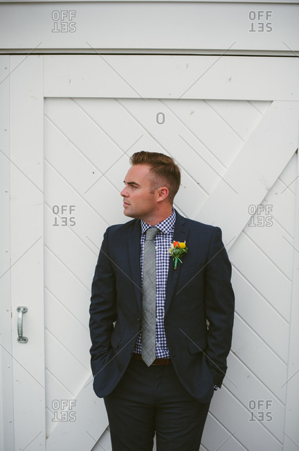 Close-up of groom standing at white barn door