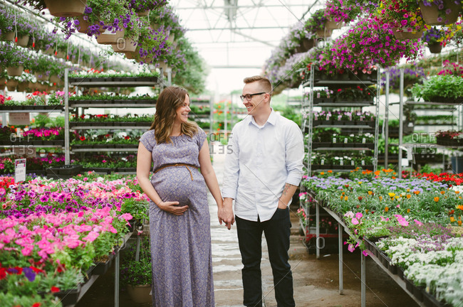 Expectant parents surrounded by flowers in garden center
