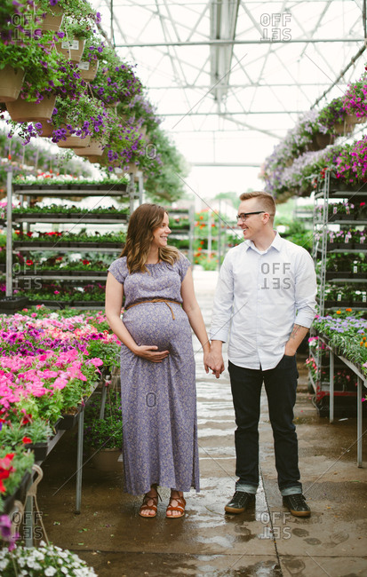 Portrait of an expectant couple in a garden center