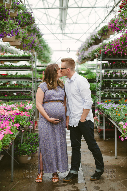 Man kisses his expectant wife in garden center