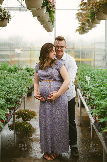 Expectant couple surrounded by plants in greenhouse