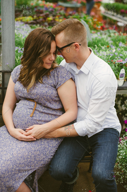 Affectionate expectant parents embrace while sitting in greenhouse