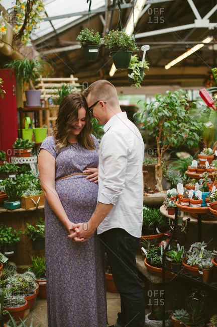 Pregnant couple share a tender moment in greenhouse